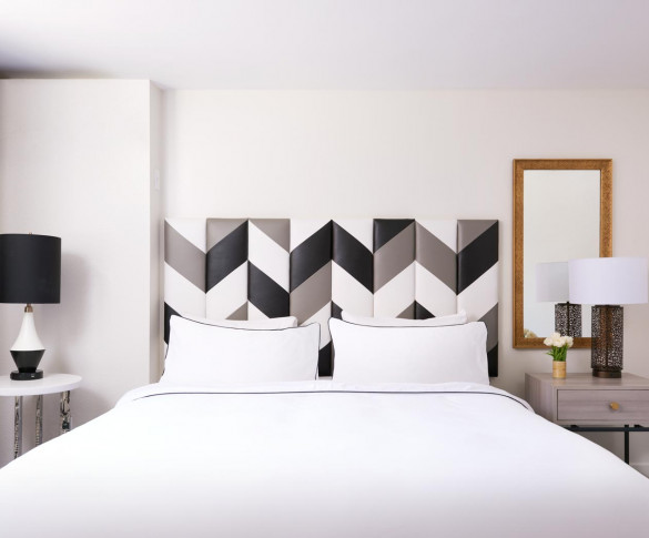 bedroom area of the ada suite with a chevron patterned headboard  white linens and two nightstands
