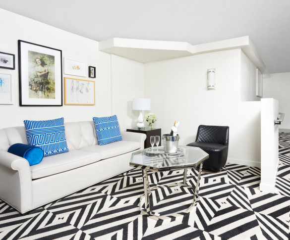 living area of the ada suite with a fun  geometric patterned carpet white couch and blue accents