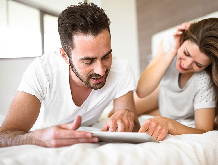 man and woman looking at ipad on bed