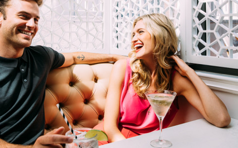 couple laughing over cocktails at fits
