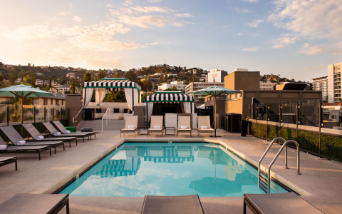 rooftop pool with lounge chairs and cabanas overlooking the hollywood hills