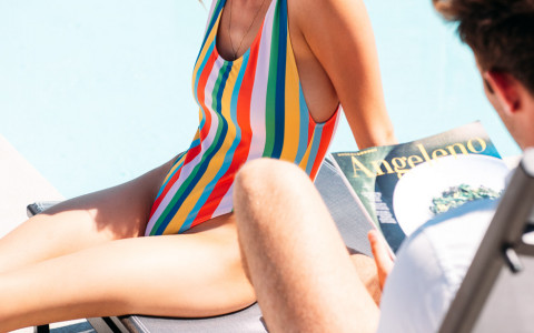 woman in a striped one piece bathing suit sitting on her boyfriends lounge chair at the pool