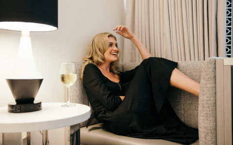 blonde woman in on the couch in a suite next to a glass of wine