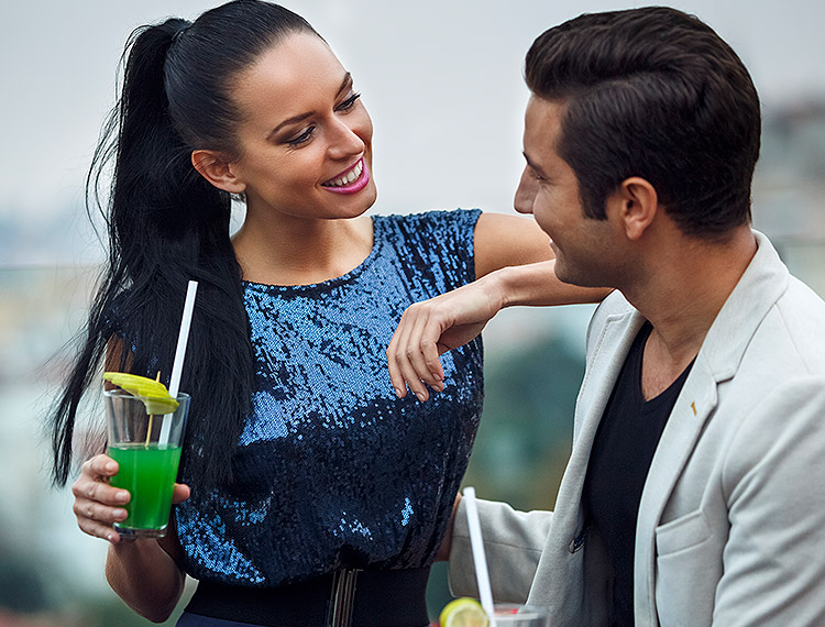 woman with long black hair smiling at a man holding green cocktails