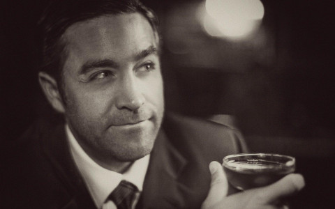 handsome man holding cocktail black and white