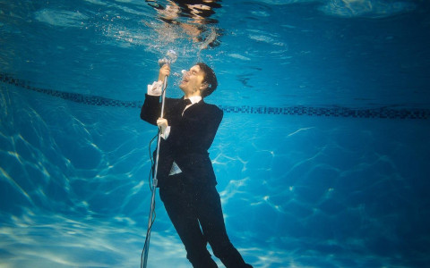 man in suit singing into a microphone under water