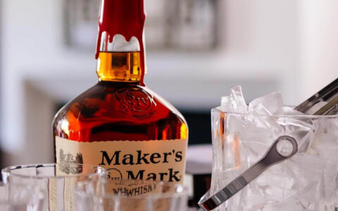 bottle of makers mark, glasses and bucket of ice