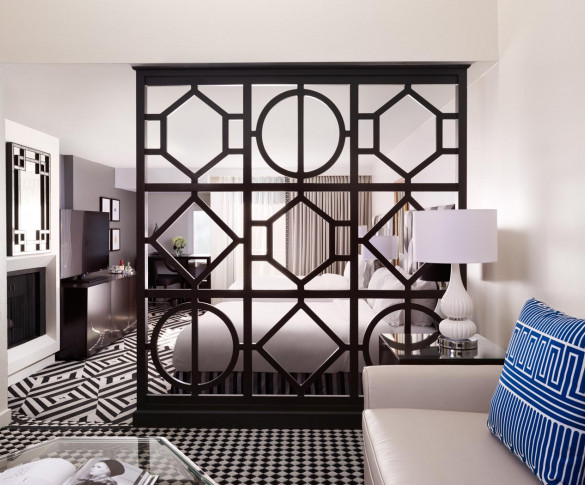 executive queen suite living area and bedroom area separated by a geometric patterned open wall
