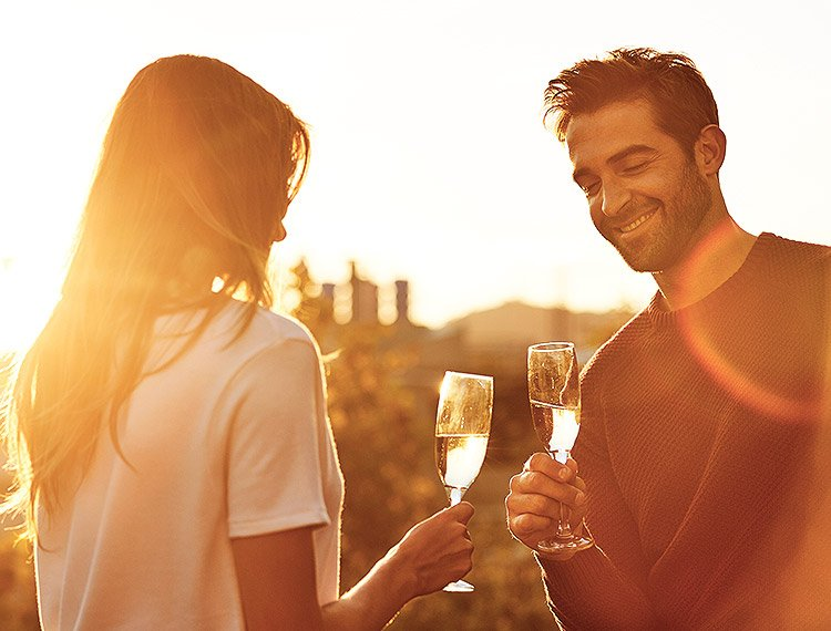 Man and woman clinking champagne glasses together