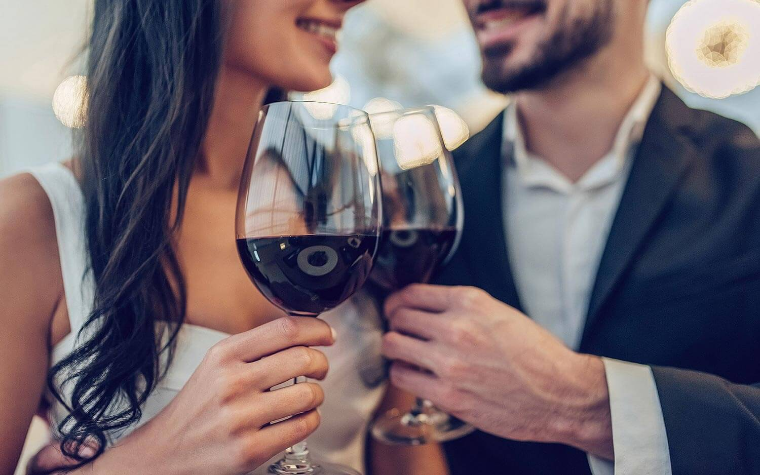 Man and woman clinking wine glasses together