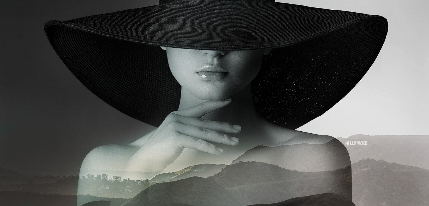 woman wearing large hat in black and white