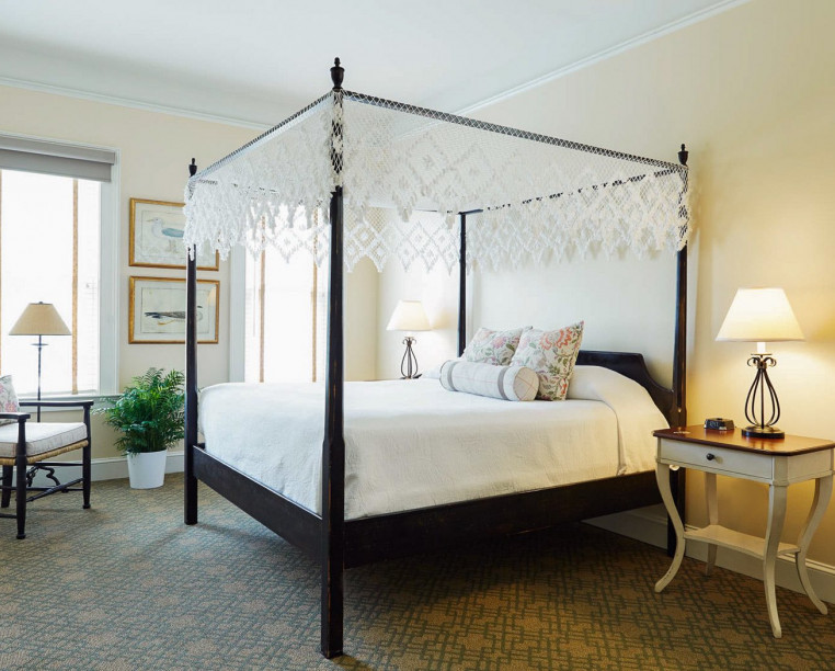 Charming Inns Fulton Lane Inn queen canopy bed with accent chair and side table