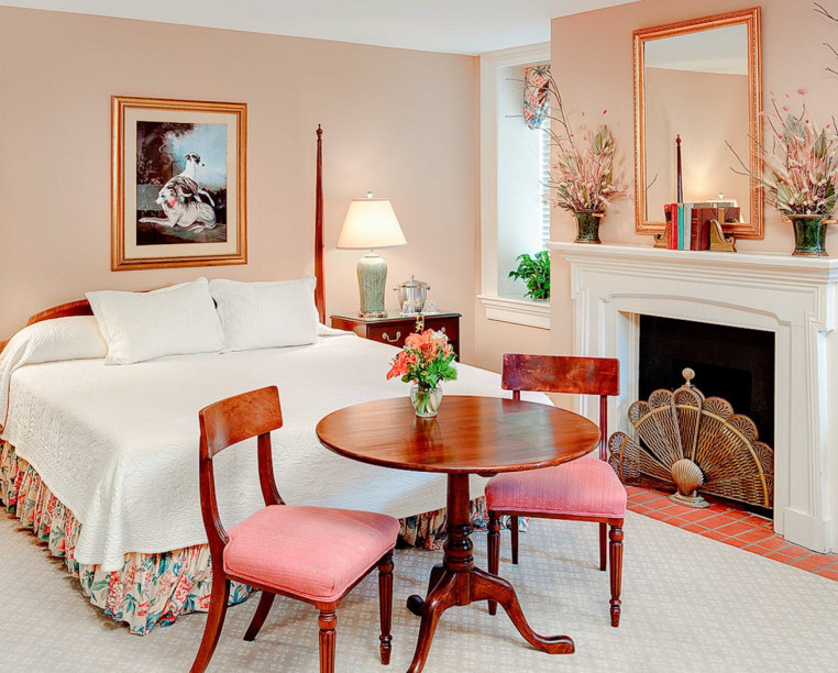 Charming Inns John Rutledge House queen bed with blush pink wall accent furniture and fireplace