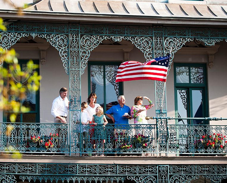 family sitting on the roof top of the john rutledge house with a flag