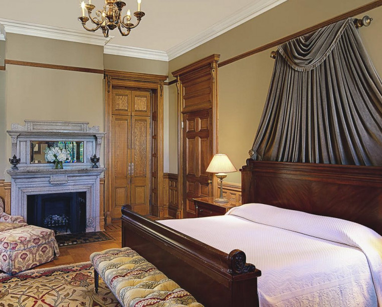 Charming Inns Wentworth Mansion large king bed with vintage accent furniture and fireplace
