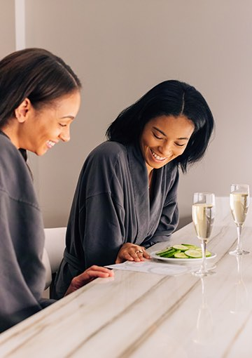 two guests in grey robes with champagne and cucumbers looking at menu