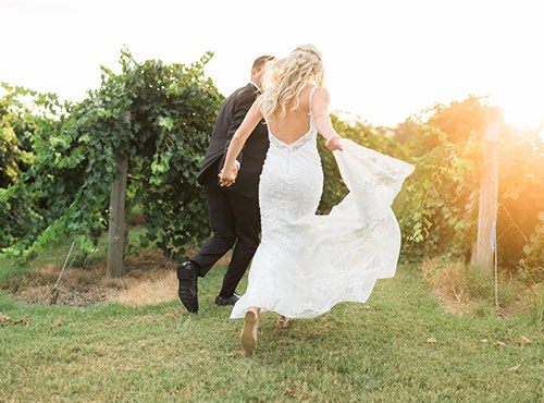 bride and groom running around the fields