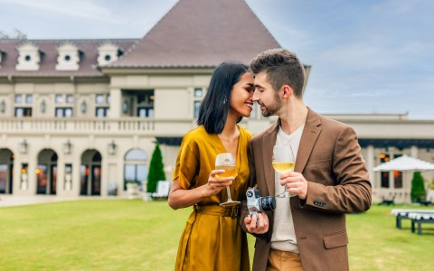 couple in front of chateau elan holding wine glasses and kissing