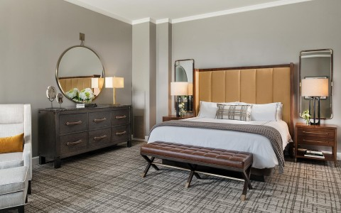 bed in suite with dresser and round mirror hanging over it