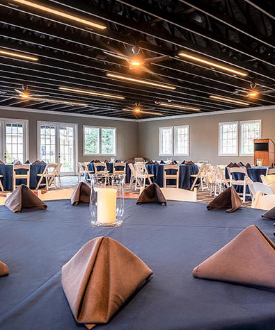 banquet tables in an event pavilion set with triangle folded napkins and a podium at the front of the room