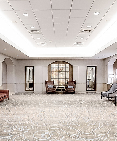 lobby area outside of event spaces with arm chairs by walls