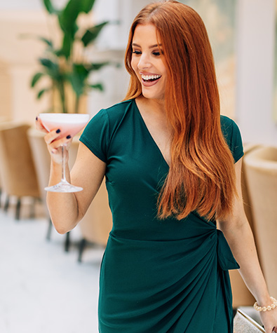 woman in a dark green dress carrying her light pink cocktail