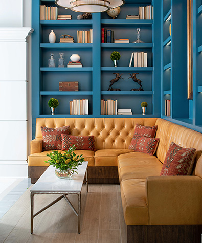 L-shaped couch up against blue colored bookcase