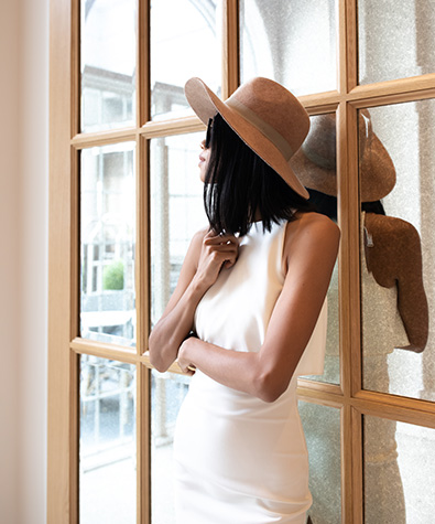 woman in white dress and floppy hat leaning up against mirrored windows