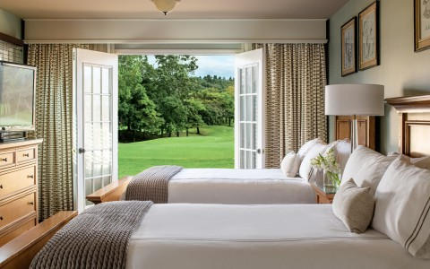 two beds with french doors opening up to green lawn