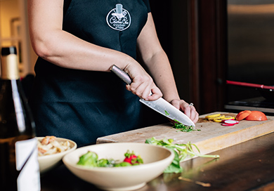 person using a large knife to chop up greens