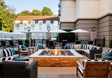 fire pit outside by the pool with seating around it