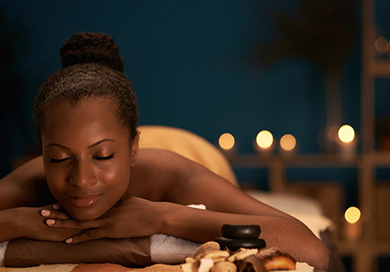 woman laying down on her stomach on a massage table at the spa