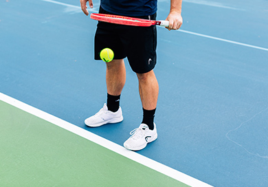 man bouncing a tennis ball with his racket on the court