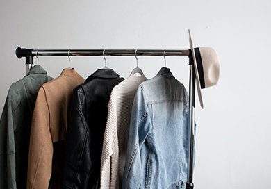 items of clothes hanging on a clothing rack with a hat on the corner