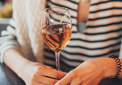 person holding a glass of rosé