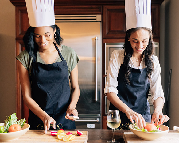 two women wearing chef hats and aprons putting together a salad