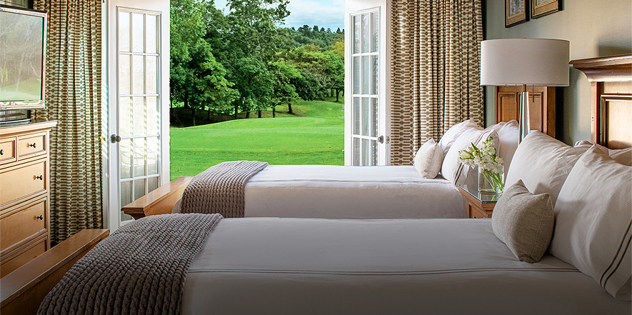 two beds in a room with open french doors looking out over a golf course