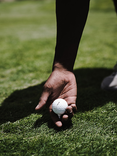 person placing golf tee with ball on it between their fingers