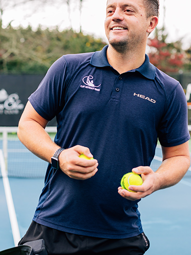 coach looking away and smiling while holding two tennis balls