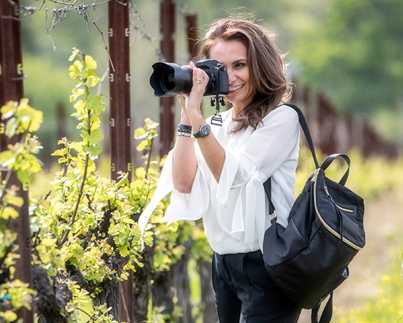 woman outside holding her camera bag and looking through the lens of her camera