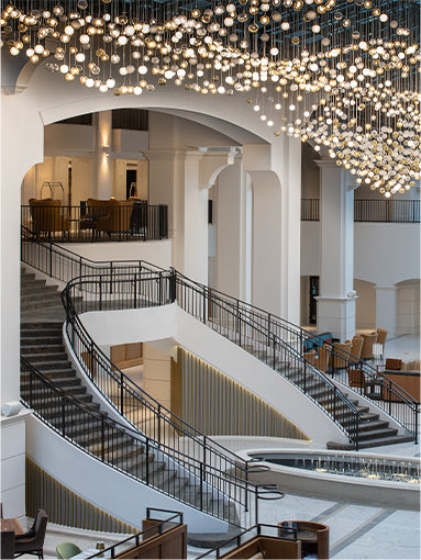 atrium with hanging lights and a double staircase