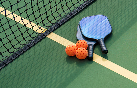 two pickleball rackets and three pickleballs laying on the court