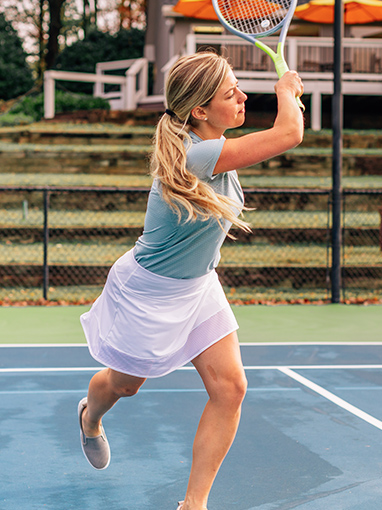 woman actively swinging at a tennis ball