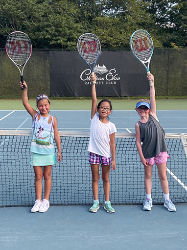 group of young children on the tennis court posing with their tennis rackets in the air