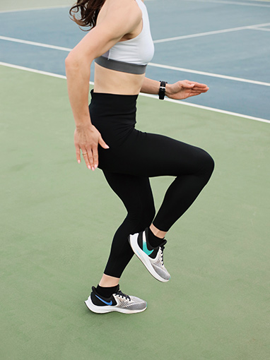 person doing high-knees on the tennis court