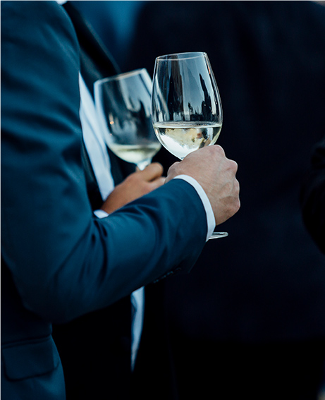 two men in suits holding glasses of white wine