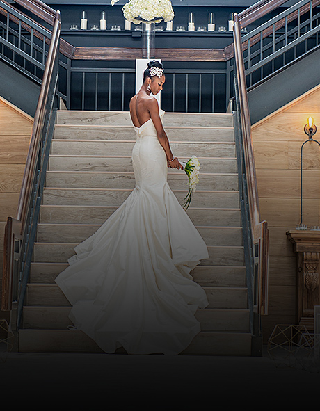 bride in a trumpet style dress on the stairs looking over her shoulder