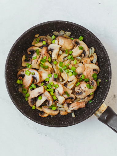 Mushrooms cooking in a fry pan with chives and onions