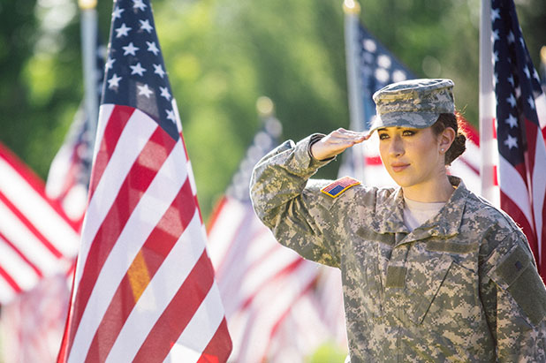 Woman in army uniform next to American flag