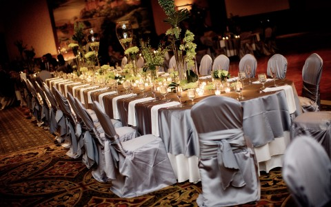 Long table with lit candles & silk wrapped chairs
